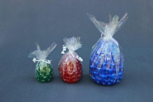 """Žvakė """"Kankorėžis"""", trijų dydžių, įvairių spalvų: mėlyna, žalia, raudona, balta, supakuota į celofaną."""