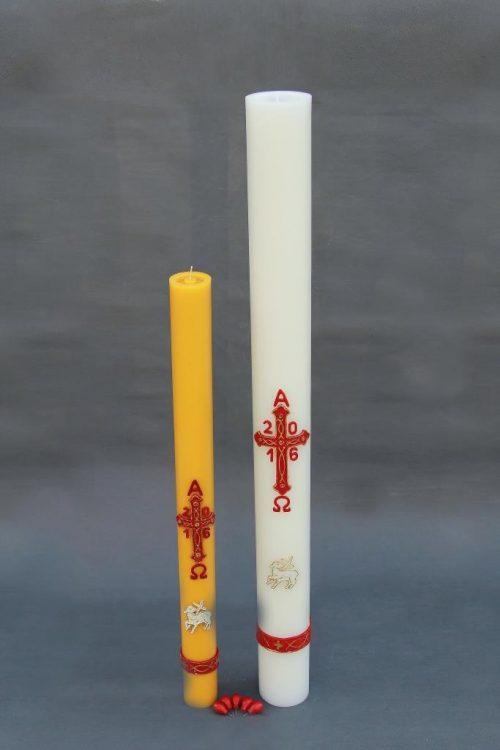 baltos arba geltonos spalvos velykinė žvakė (paschalas), dekoruotas bareljefiniais paveikslais, supakuotas į dėžutę kartu su spurgiukais.