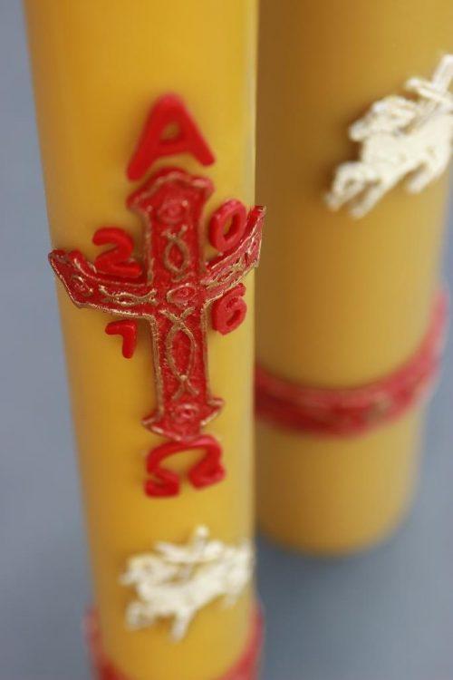 natūralaus vaško velykinė žvakė (paschalas), dekoruotas bareljefiniais paveikslais, supakuotas į dėžutę kartu su spurgiukais.